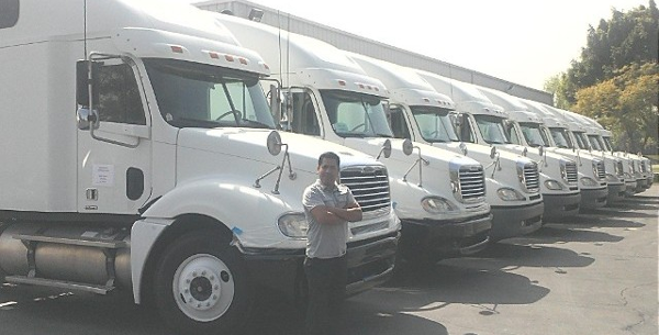 Man standing in front of trucks
